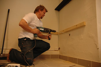 Handy man drilling into wall