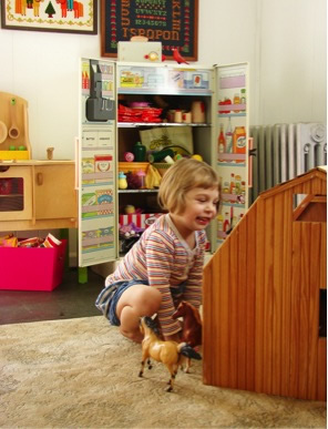 little girl playing with toys in room